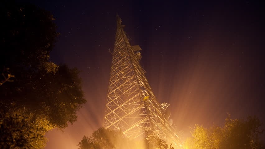 HD Time Lapse of Fog Illuminated With Shafts Of Light Rays Below A CommunicationsTower Antenna, Trees And Night Stars