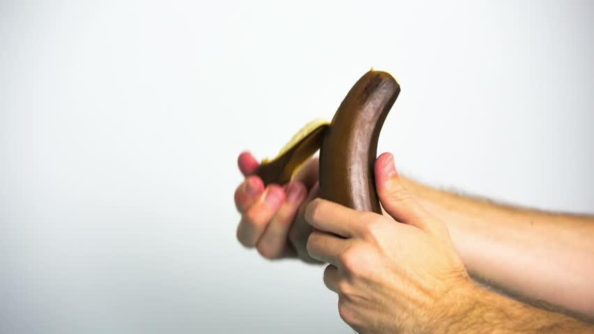 Peeling black banana close up. Hands peel of black banana on white background. - HD stock footage clip