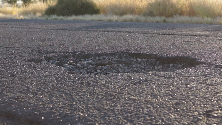Many vehicles passing over top of and dodging a large pothole in the asphalt pavement on a busy street.