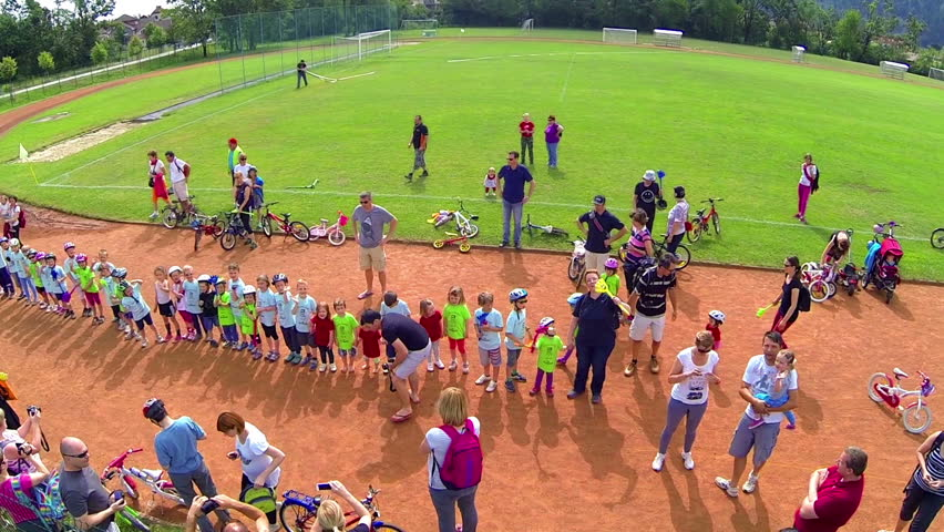 VRHNIKA, SLOVENIA - AUGUST 2014: Kids standing in line and waving to flying camera. Youngsters waiting for reward for finishing bicycle competition. - HD stock footage clip