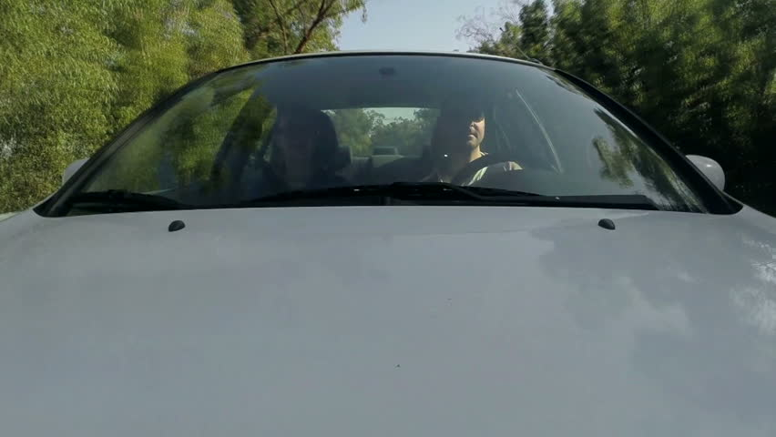 Couple riding in car on beautiful road, front view.
