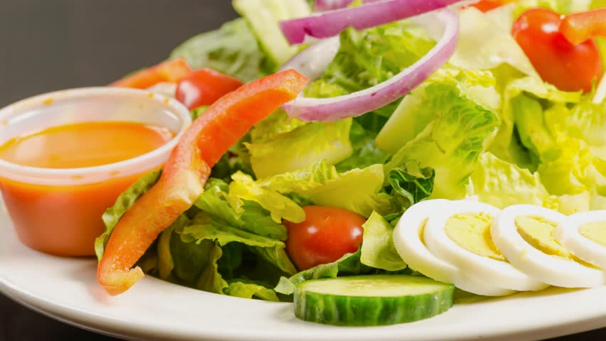 Delicious garden salad served in a restaurant, fresh green salad with lettuce,cherry tomatoes,boiled egg,onions,pepper,french dressing and cucumbers