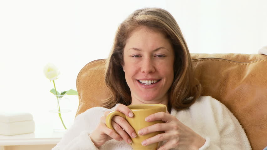 Woman sitting on couch drinking coffee - HD stock video clip