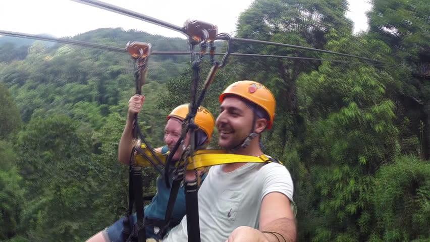 Tourists enjoying on ZIPLINE. Zip-line attraction.