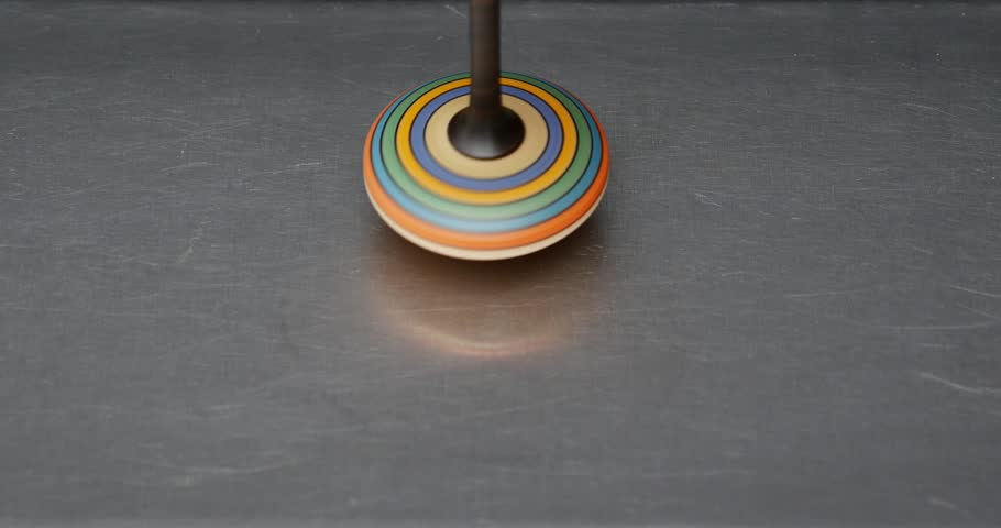 4K footage of a spinning top spinning on a silver surface/Let us play with a spinning top - 4K stock video clip