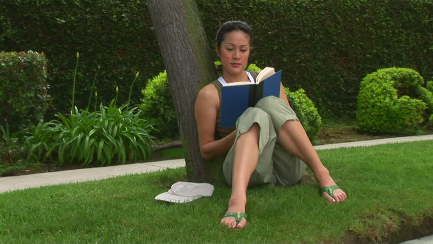 Young woman reading a book in the park - HD stock footage clip