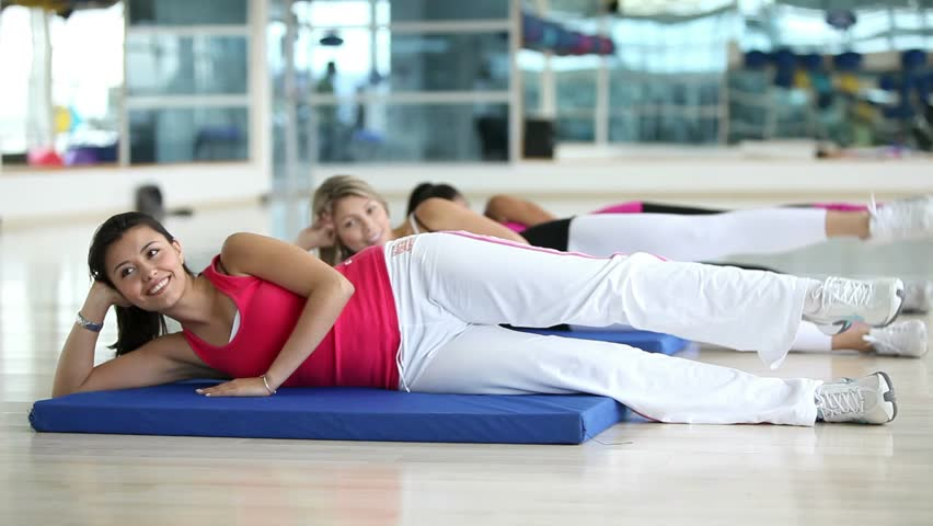 Group of women lying on the floor exercising at the gym  - HD stock video clip