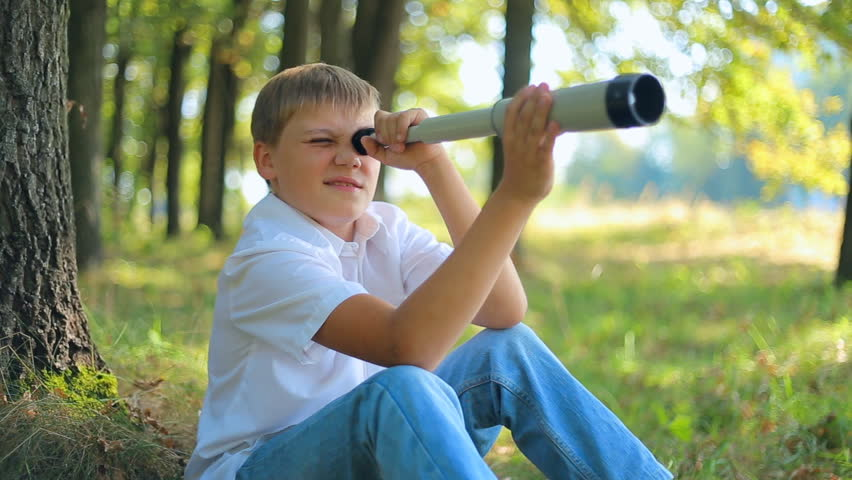 teenager boy looks through a telescope