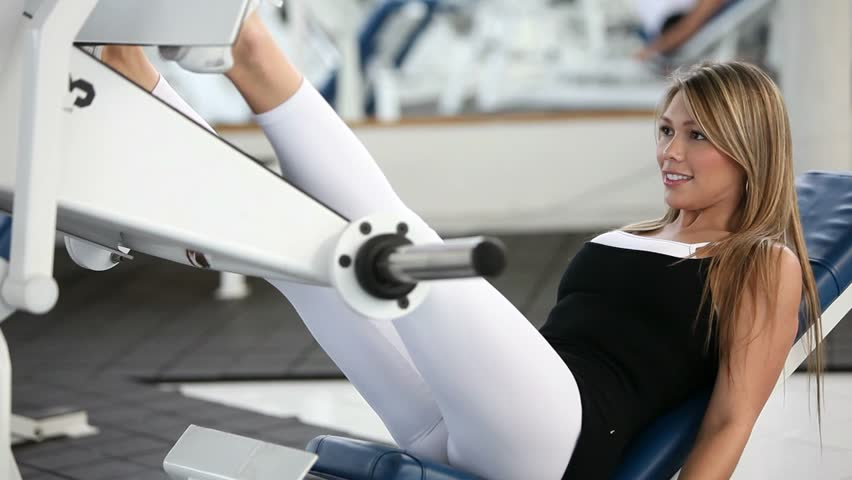 Woman at the gym exercising her legs on a machine  - HD stock video clip