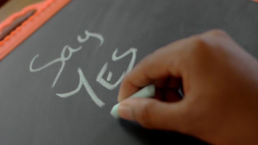 a person writing on a black cardboard slate with a chalk say yes to life