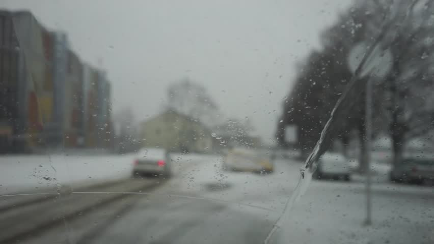 The car goes on the road against the background of a blizzard of snow through droplets on glass machine - HD stock video clip
