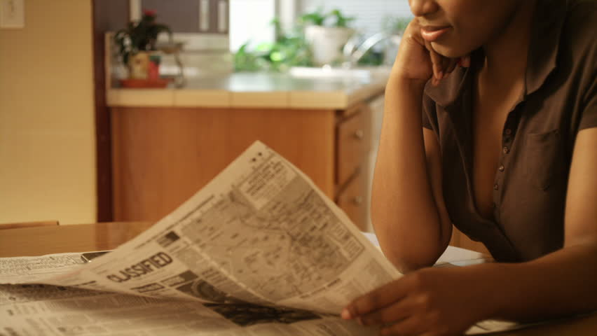 An African American woman performs various tasks around the house. She searches for a job, pays bills, makes coffee, studies the bible, reads a book, and works on her laptop. - HD stock footage clip