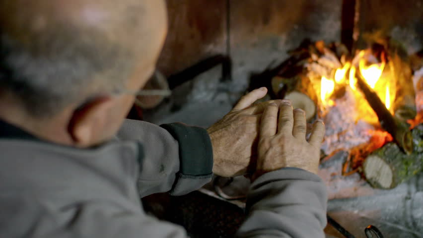 old man warms up his hands to the fire in the fireplace - 4K stock footage clip