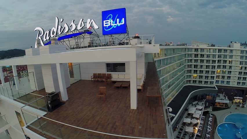 SOCHI - JUL 26, 2014: Edifice of Radisson Blu hotel with signboard on roof at summer evening. Aerial view. 3.7 million travellers visited town resort Sochi from january to august 2014