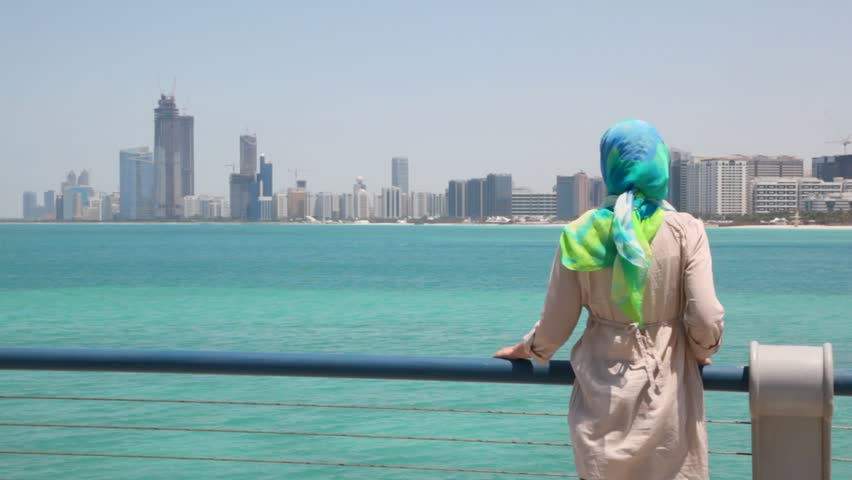 young woman stand on shore and looks at skyscrapers in Abu Dhabi, UAE - HD stock video clip
