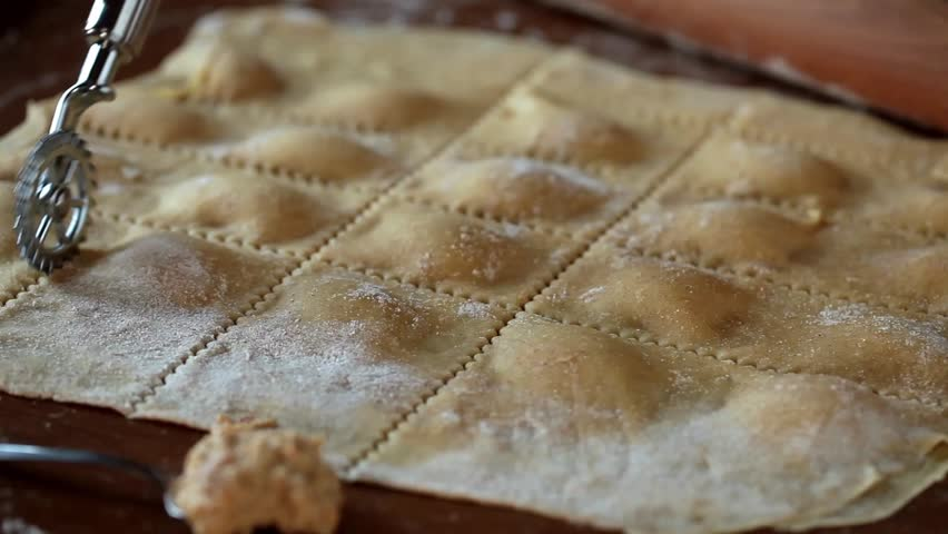 Video clip showing the process of cut homemade agnolotti pasta with a pastry wheel.