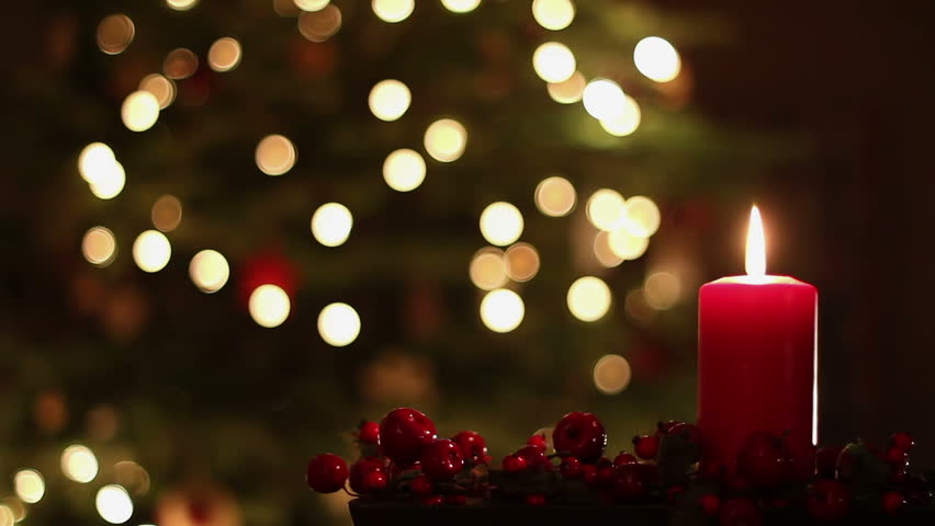 Female Hand Lighting A Candle. Christmas Tree In The