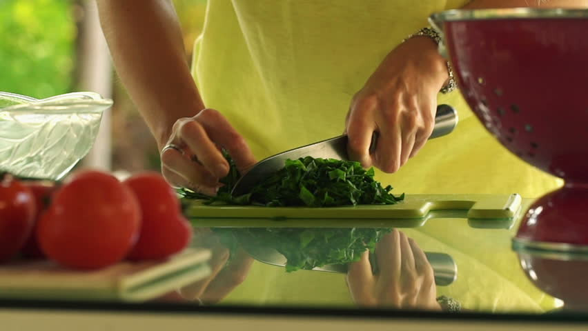 Close up of woman hands cutting spinach, slow motion shot at 120fps
