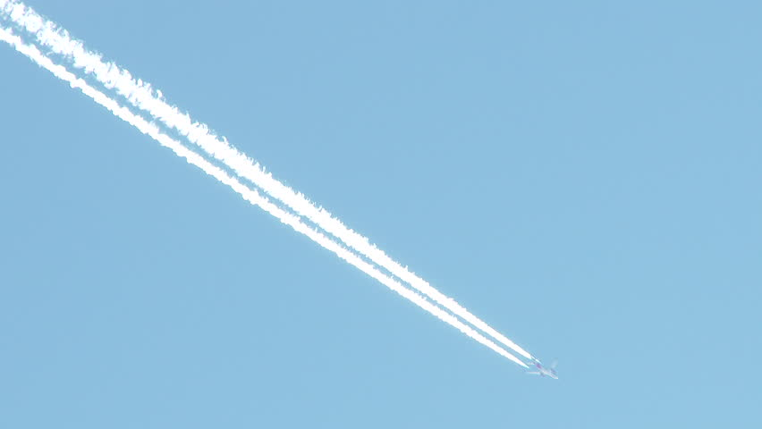 4K - Airplane flies overhead through frame on clear, blue sky day leaving behind vapor trail jet contrails. - 4K stock video clip