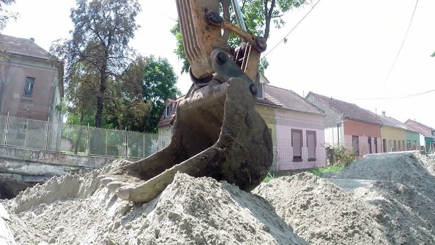 Excavator Bucket on a Big Pile of Sand.Bucket excavator with big pile of sand