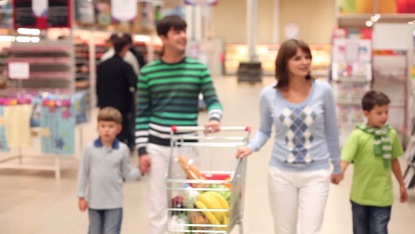 A family of four rolling a trolley with products along the supermarket, looking around and talking