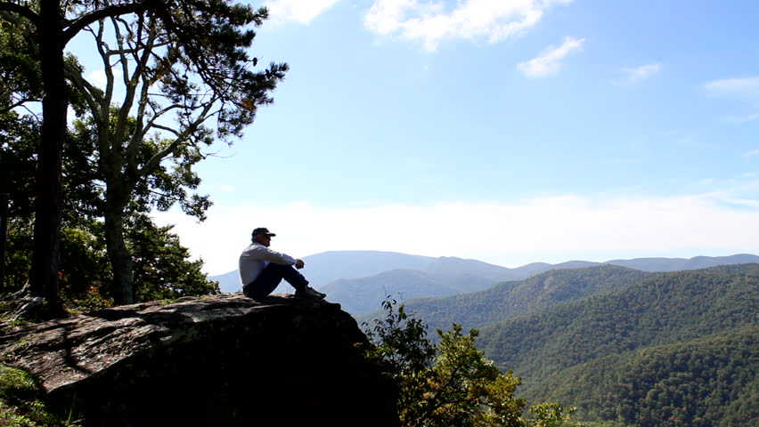 Senior man sits alone on 20-Minute Cliff overlook along the  Blue Ridge Parkway, looking out over the Blue Ridge Mountains which is located in the George Washington National Forest in Virginia. - HD stock video clip