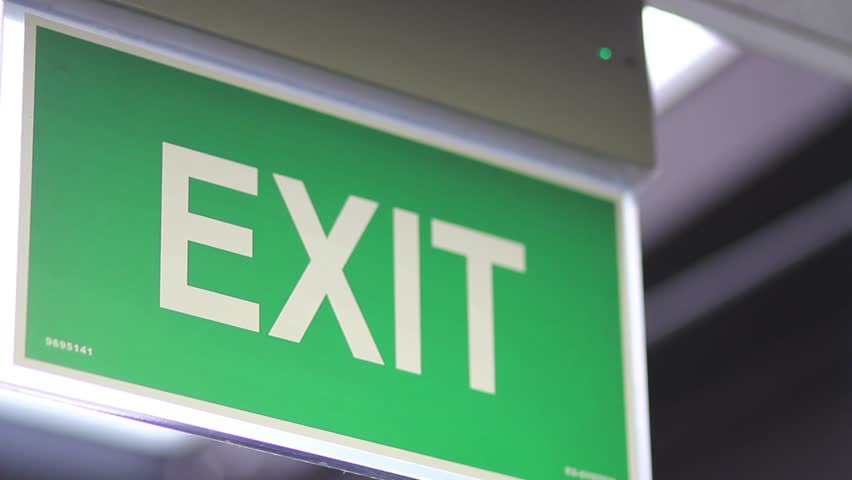 A close up shot of an emergency exit sign which goes into focus and out of focus/Exit sign