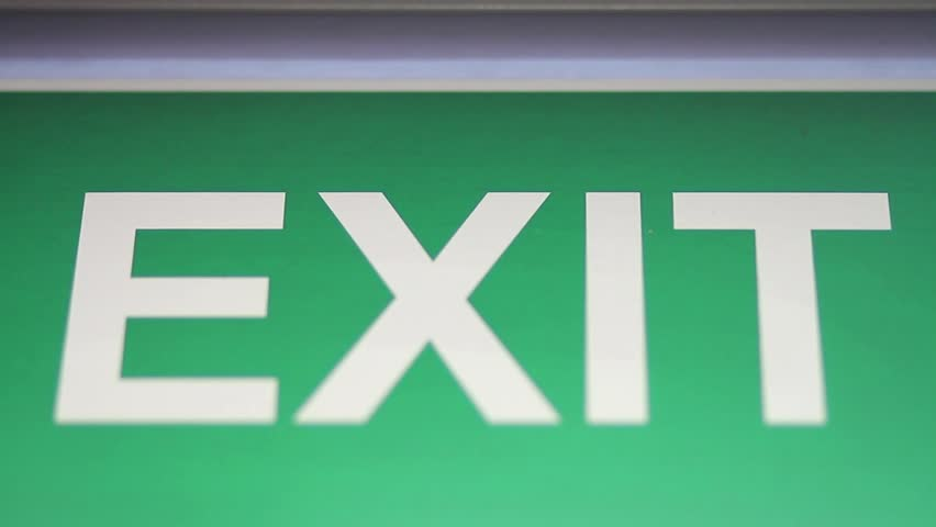 A close up shot of an emergency exit sign which goes into focus and out of focus/In case of an emergency this is your safe way out