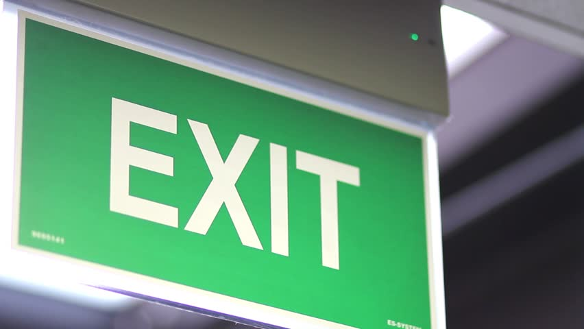 Side shot of an emergency exit sign - it goes into focus and out of focus/This is an emergency exit