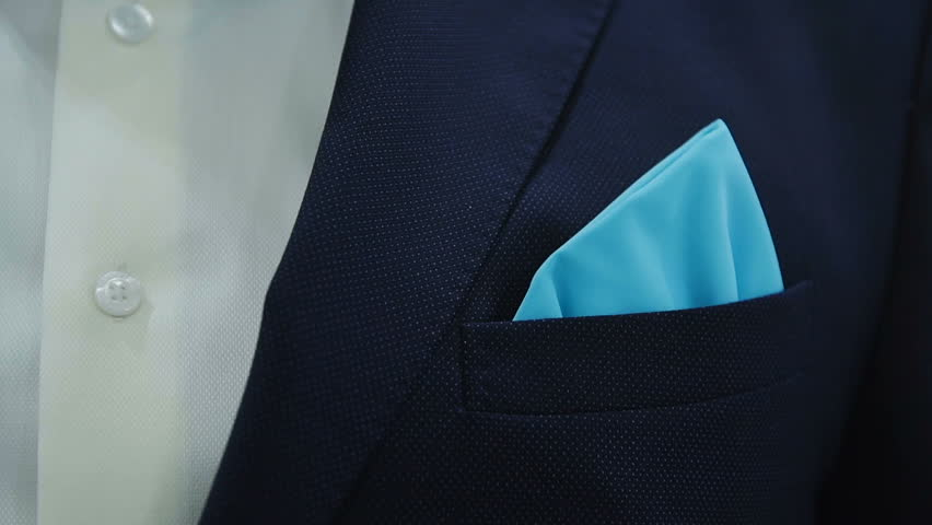 the man adjusts his blue scarf on black jacket close up
