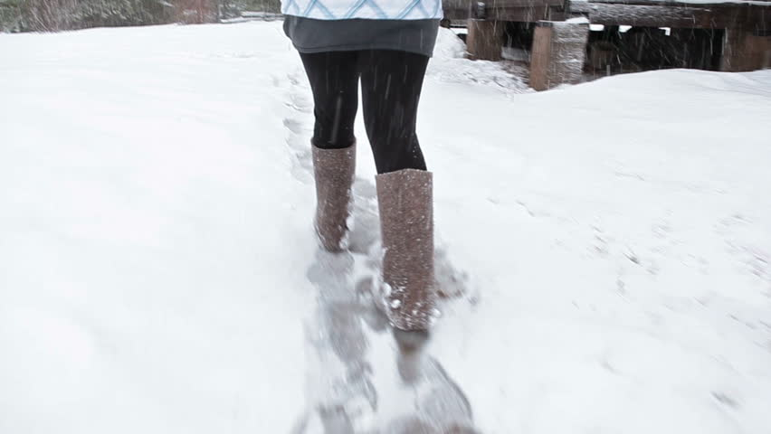 Female legs wearing felt boots walking on snowy pathway at winter