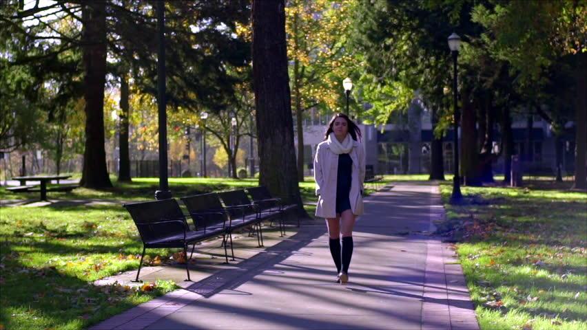 Mixed Race Young Woman Walks Through City Park Toward Camera (Long Shot)