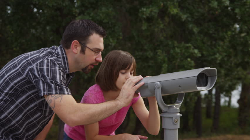 Father and daughter looking through viewer