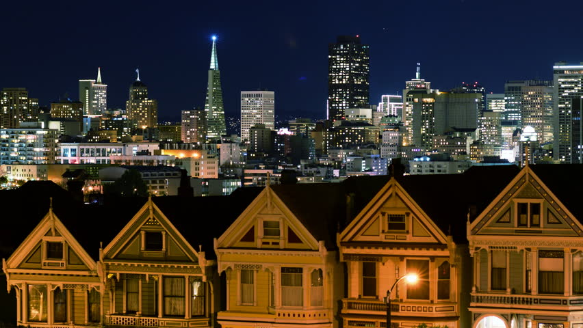 "4K Time lapse footage of iconic ""Postcard Row,"" traditional Victorian style houses and skyline at night in San Francisco, California"