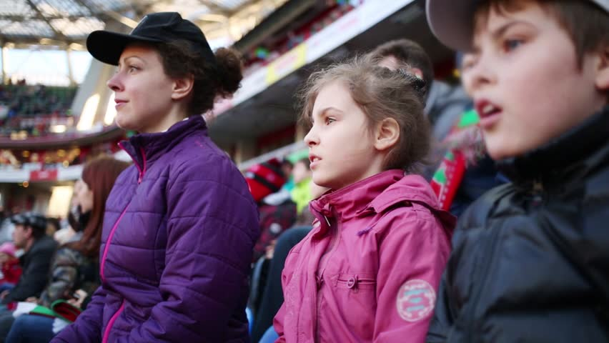Mother, daughter and son attentive look football match at stadium - HD stock footage clip