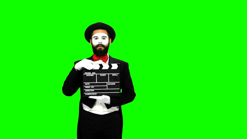 Happy, bearded, young man mime sneezes and using the movie clapper on green screen