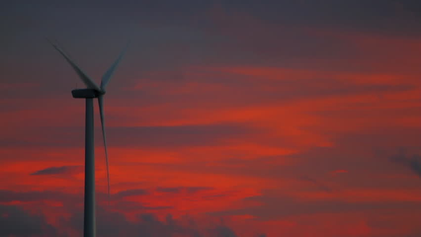 Lone Wind Turbine with sunset and sky offset to left. - HD stock video clip