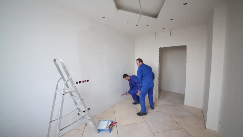 Two workers renovating a room, one puts the ladder against the wall and climbs up on it - HD stock video clip