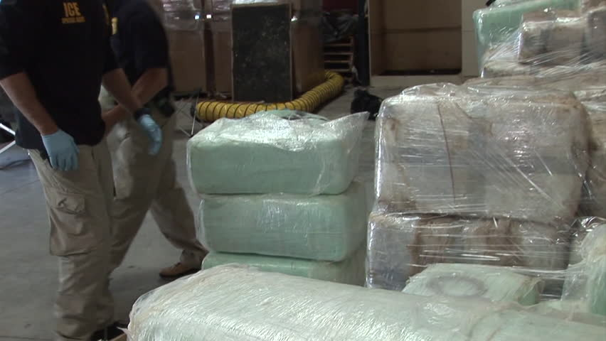CIRCA 2010s - DEA agents stack confiscated drugs in a warehouse.