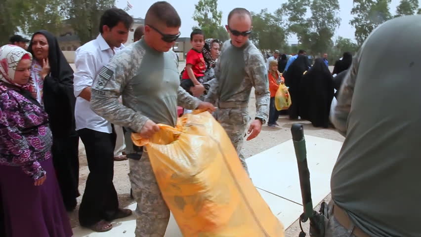 CIRCA 2010s - U.S. soldiers hand out food, toys and school supplies to people in Baghdad, Iraq.