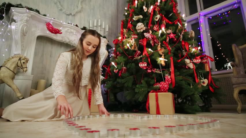 Teenage girl sits on floor near Christmas tree and puts candles in shape of heart | Shutterstock HD Video #9188390