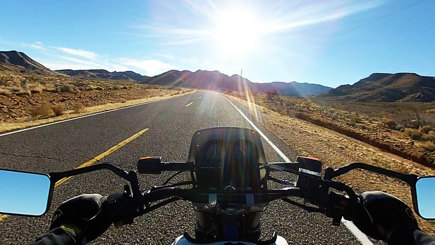 Viewpoint or point of view of a motorcyclist riding into the sunset on a desert highway. An empty road provides a scenic view of a rugged desert landscape. | Shutterstock HD Video #9227315