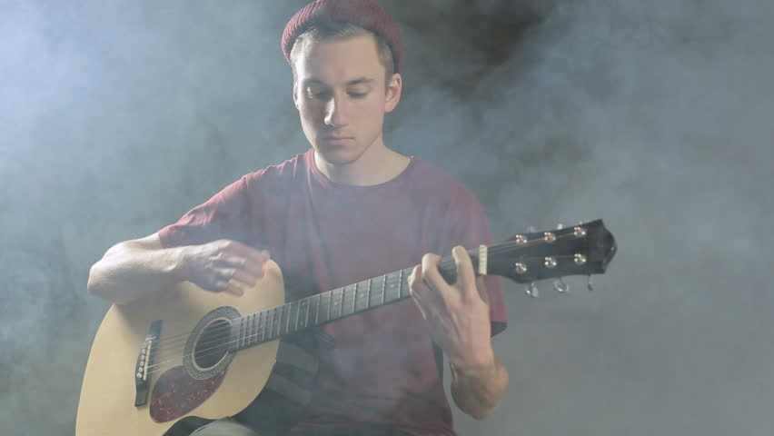 Talented young musician playing guitar in dark studio in smoke - HD stock footage clip