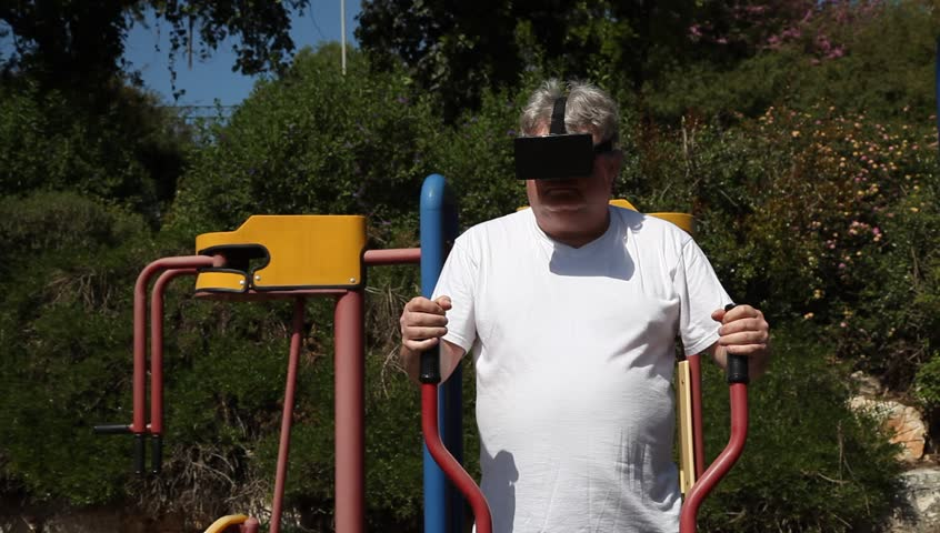 A big man with 3D VR head mounted display in outdoor gym. The athlete watches a movie while getting an exercise. - HD stock footage clip