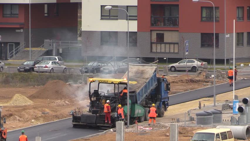 VILNIUS, LITHUANIA - NOVEMBER 17, 2014: Asphalt spreader, roller and truck machines on November 17, 2014 in Vilnius, Lithuania. Road pavers workers with special equipment. Static shot on Canon XA25. - HD stock video clip