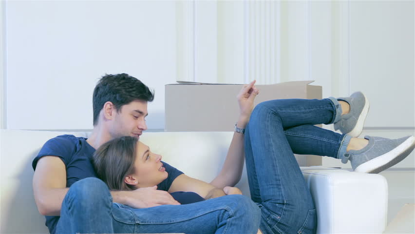 Moving home and repair of a new life. Couple in love lying on sofa among boxes for moving while man and woman hugging together in an empty apartment