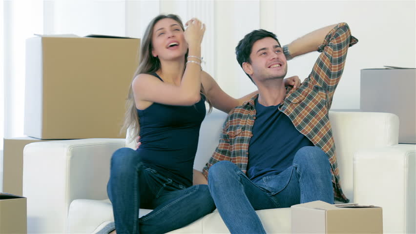 Moving, repairs, new flat. Couple girl and guy lie on the floor in the arms and showing okay thumbs up while man and woman lying on the floor among the boxes in an empty apartment view from above