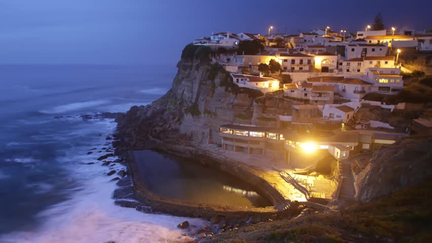 Picturesque sunset time lapse of a village located spectacularly on the ocean coast's cliff with a natural swimming-pool