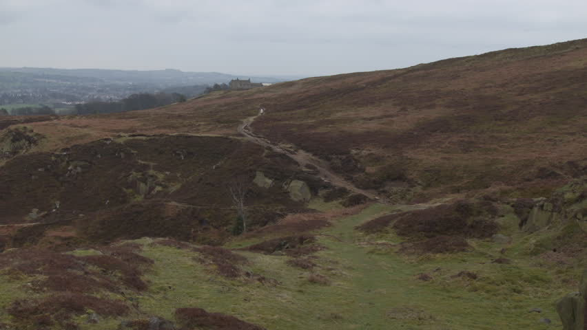 Bleak Moorland landscape scene HD stock footage. A beautiful establishing shot of a Yorkshire moor with two people walking up the natural track. Filmed on the BMD Cinema Camera. ProRes 422.