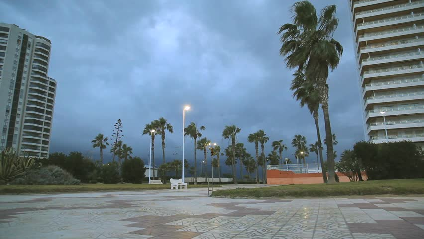 Panoramic view of the main promenade in the city Cullera at dusk during the bad weather in the winter, palm trees swaying in the wind, big hotels - HD stock footage clip